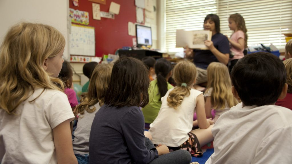 Teacher reading a book to young students.